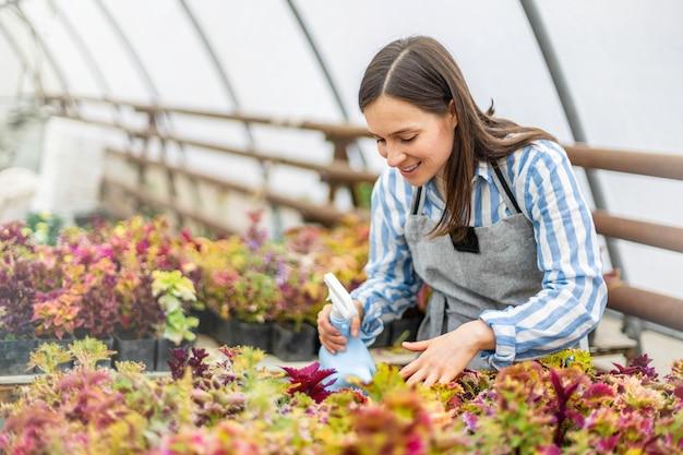 Fiorista donna nella piantagione di fiori d'acqua del grembiule usa l'annaffiatoio sorridendo godendosi la coltivazione