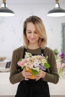 Fiorista donna in un grembiule nero che tiene un mazzo di fiori