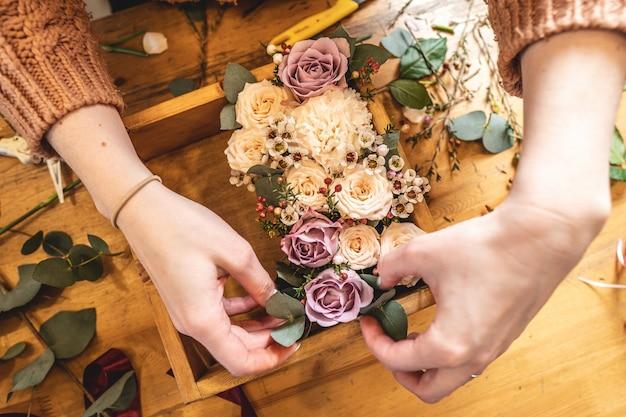 Fiorista donna raccoglie una composizione floreale in una scatola di legno con le mani