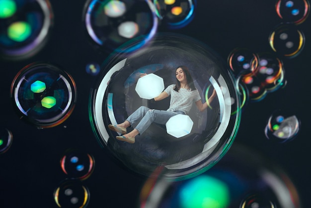Donna che vola in una grande bolla di sapone, felice fantasia