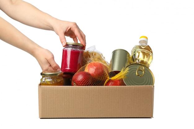 La donna piega i prodotti in scatola di donazione, isolata su spazio bianco