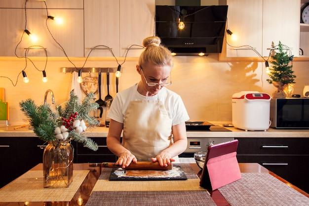 La donna segue la ricetta sulla tavoletta digitale e stende l'impasto con un mattarello per cucinare i biscotti di panpepato di natale nella sua cucina