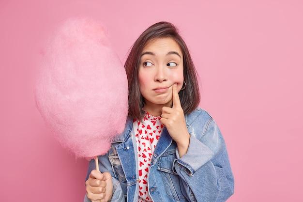 La donna forza il sorriso tiene il dito vicino all'angolo delle labbra guarda tristemente lo zucchero filato si sente sola indossa una giacca di jeans denim