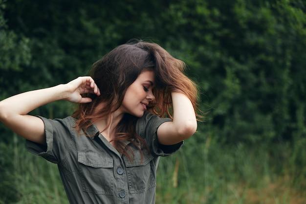Donna nella foresta abito verde si aggrappa ai capelli in viaggio di aria fresca foglie verdi vista ritagliata