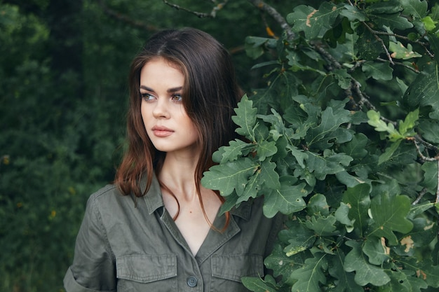 Donna nella foresta guarda al lato del cespuglio verde vista ravvicinata di aria fresca ritagliata