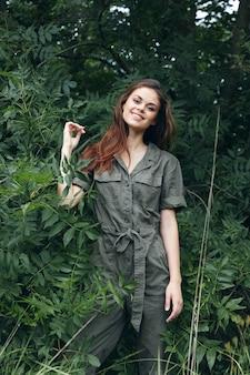 La donna nella foresta sorride e ha alzato la mano sulla vista ritagliata dell'estate