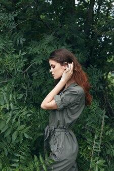 La donna nella foresta tocca i capelli sulla testa e la vista laterale della natura della tuta verde del paesaggio