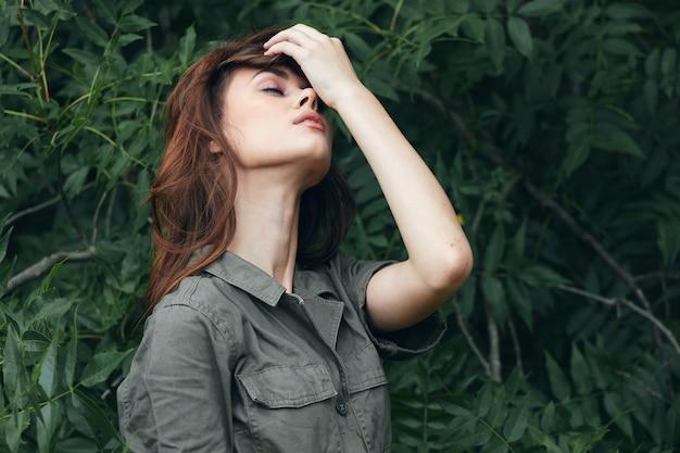 Donna nella foresta con gli occhi chiusi, tiene una mano vicino alla vista ritagliata della natura del viso