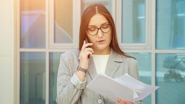 Donna in abito formale e occhiali parlando al telefono e guardando i documenti, in piedi per strada.