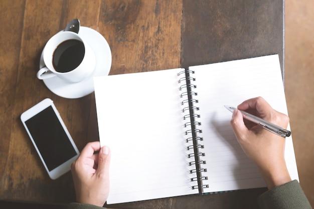 Giornale di scrittura della mano di lavoro libero professionista della donna sul blocchetto per appunti del piccolo taccuino nella caffetteria