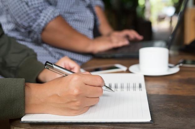 Giornale di scrittura della mano di lavoro libero professionista della donna sul piccolo taccuino