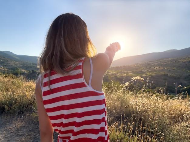 Donna da dietro che punta il dito verso il sole. copia spazio. paesaggio delle montagne.