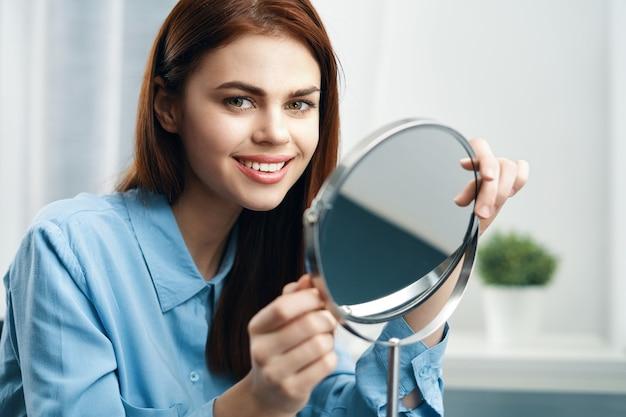 Donna davanti allo specchio cosmetici dermatologia trucco cura della pelle