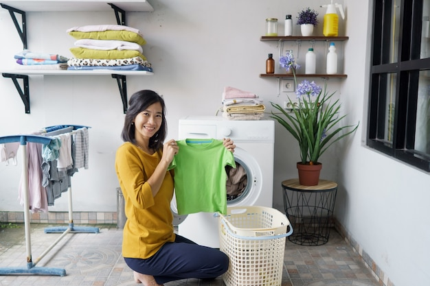 Donna davanti alla lavatrice che sorride alla macchina fotografica mentre fa un po 'di biancheria caricando i vestiti all'interno
