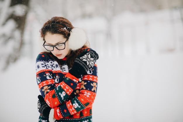 La donna si bloccò e sospirò con le mani per scaldarle. ragazza sul paesaggio invernale in città. la donna si bloccò vicino al parco nel freddo inverno