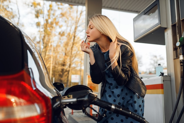 La donna alimenta il veicolo sulla stazione di servizio, il rifornimento di carburante servizio di rifornimento benzina, benzina o gasolio,