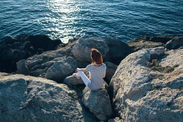 La donna in piena crescita si siede sulle pietre sulla spiaggia vicino alla vista dall'alto del mare