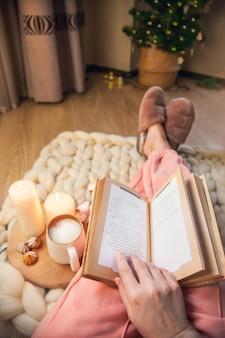 La donna in pantofole di pelliccia è sdraiata su una coperta di filato spesso, legge un libro, beve cappuccino sullo sfondo di un albero di natale con le luci. l'atmosfera di familiarità e comfort