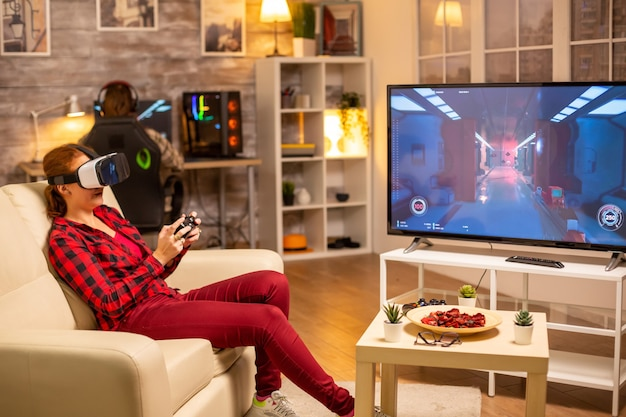 Donna giocatore che gioca ai videogiochi utilizzando un auricolare vr a tarda notte nel soggiorno