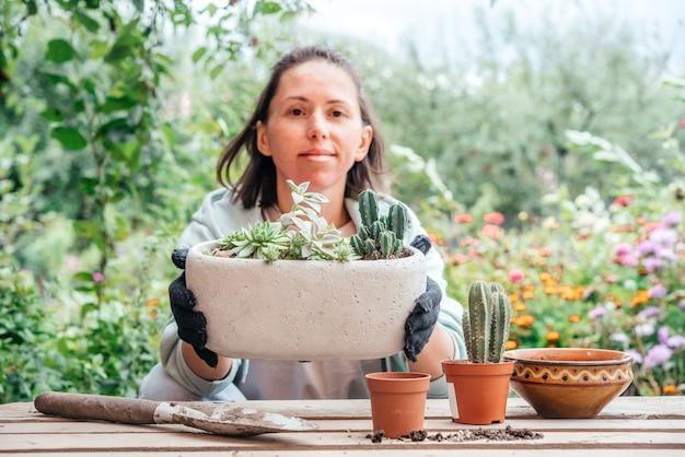 Una donna giardiniere che ripianta piante grasse e cactus all'aperto