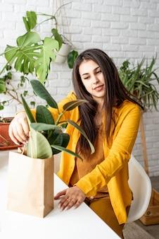 Giardiniere donna prendersi cura delle piante mettendo un vaso di fiori