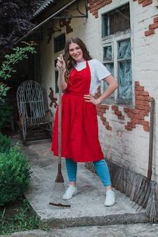 Una donna giardiniere con un rastrello si erge sullo sfondo di una casa rurale concetto di agricoltura e