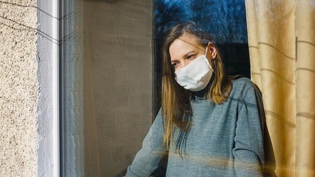 Una donna con una maschera di garza guarda attraverso la finestra