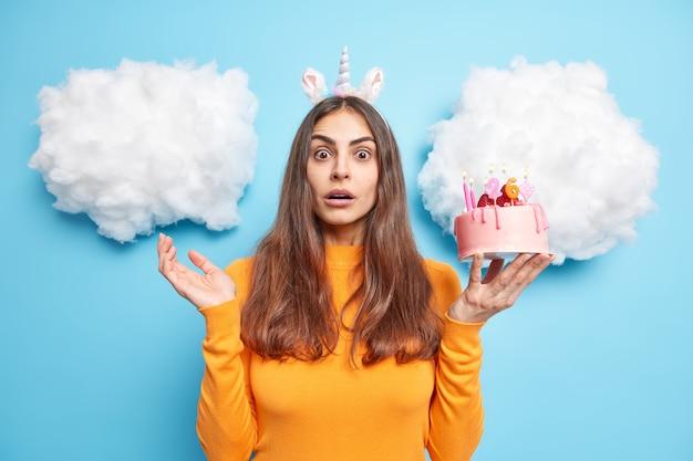 La donna guarda sorprendentemente la telecamera festeggia il 26° compleanno di una vecchia torta festiva indossa un maglione arancione isolato su blu