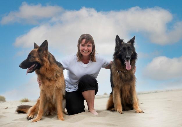 Donna e pastori tedeschi restano sulla spiaggia