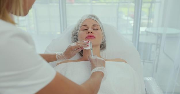 Donna che ottiene un'iniezione nelle sue labbra nel salone di bellezza. donna di iniezioni di bellezza sdraiata nell'ufficio dell'estetista. aumenta le labbra con acido ialuronico, procedura di rimodellamento, rivitalizzazione.