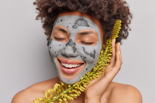 La donna ottiene una maschera facciale realizzata con ingredienti naturali a base di erbe sorride a trentadue denti tiene gli occhi chiusi sta con le spalle nude gode di pose di prodotti di bellezza al coperto. dermatologia cura della pelle