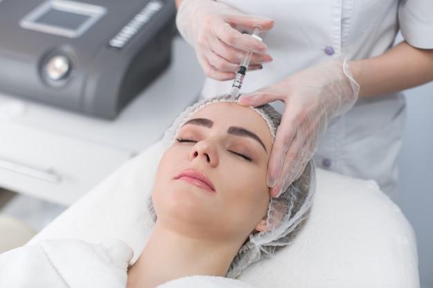 La donna riceve l'iniezione in faccia. donna di bellezza che fa le iniezioni di botox. giovane donna ottiene iniezioni facciali di bellezza nel salone di cosmetologia. iniezione di invecchiamento del viso. medicina estetica, cosmetologia