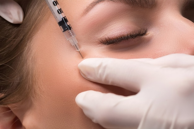 Donna che ottiene iniezione cosmetica di botulino vicino agli occhi. rughe a zampe di gallina.