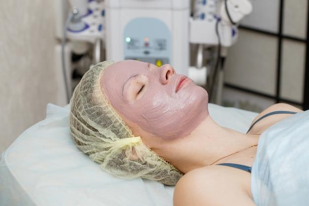 Donna che ottiene la maschera della sbucciatura del fronte nel salone di bellezza della stazione termale
