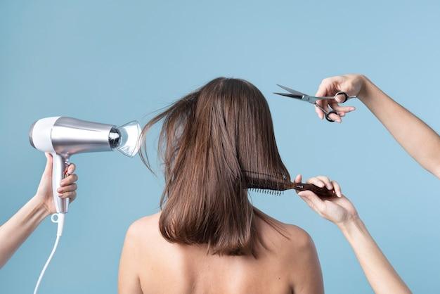 Donna che si taglia i capelli e si asciuga i capelli con il phon