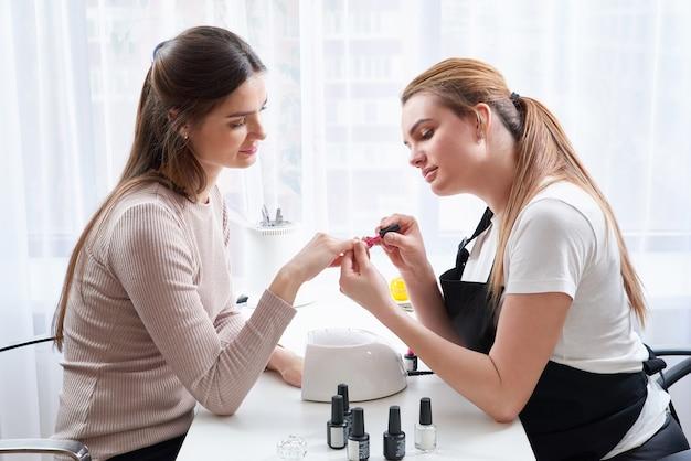 Donna che ottiene una manicure al salone del chiodo
