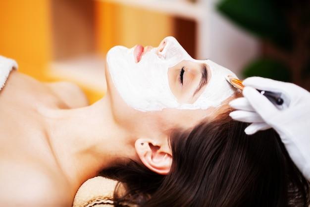 Donna che ottiene la maschera di protezione della stazione termale nel centro di bellezza