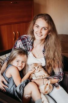 Donna e ragazza seduta su una sedia a casa e tenendo il suo cane, comunicazione con un animale domestico