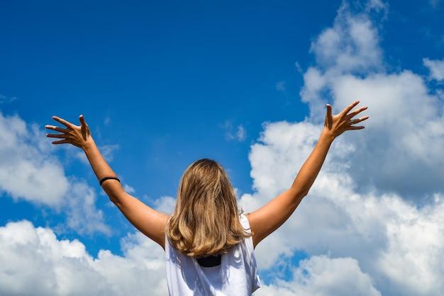 Una donna o una ragazza si alza e allunga le mani al cielo. la ragazza alzò le mani contro il cielo blu