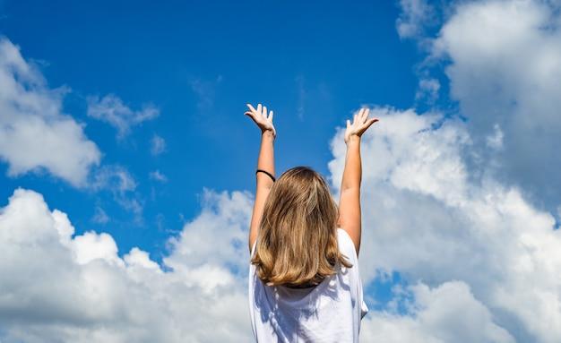 Una donna o una ragazza sta con le spalle alla telecamera e allunga le mani verso il cielo. la ragazza alzò le mani contro il cielo blu