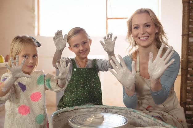 Donna e ragazze che mostrano le mani nel negozio di terraglie