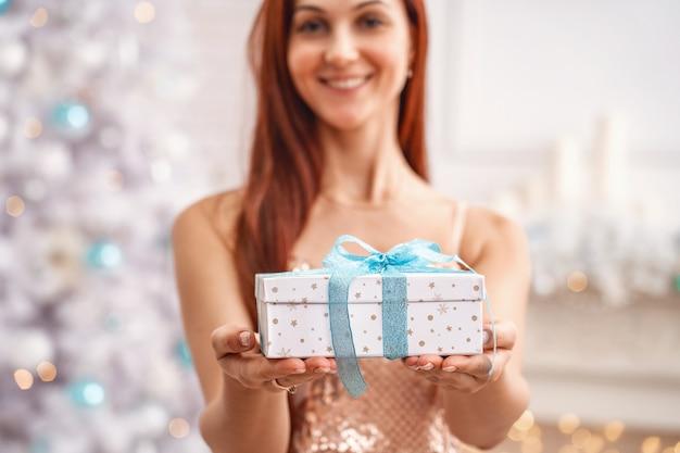 La donna dà il contenitore di regalo di natale