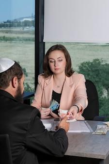 Donna che dà un mucchio di banconote in denaro uno stipendio a un ebreo con una kippah e un abito nero, rimborso in contanti in ufficio. signora d'affari che consegna nuovi sicli e banconote dalla sterlina. prestito in contanti di giorno di paga