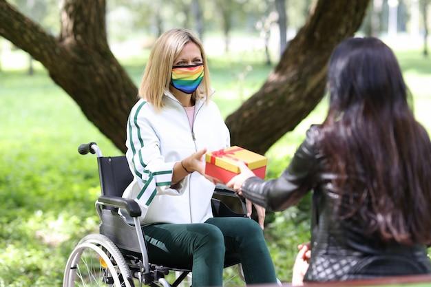 Donna che fa un regalo in scatola rossa ad un amico disabile in maschera medica protettiva con simboli lgbt in