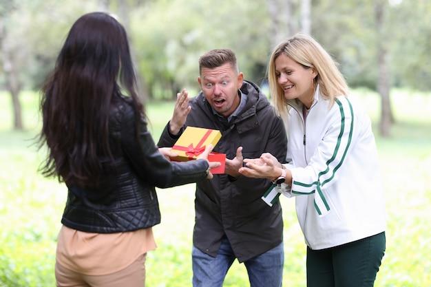 Donna che fa un regalo in scatola rossa giovane coppia nel parco che sceglie regalo per il concetto di celebrazioni familiari