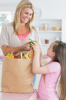 Donna che dà peperone verde alla figlia dalla borsa della drogheria