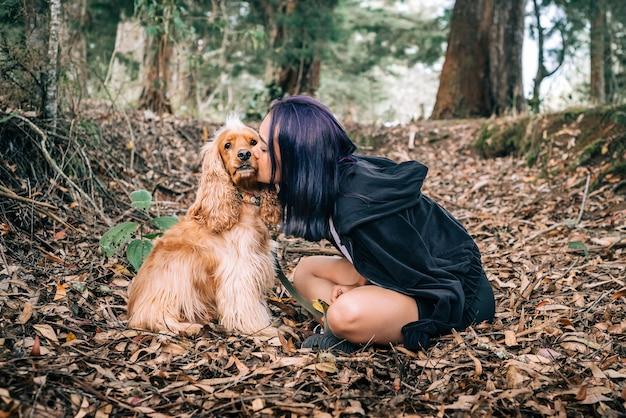 Donna che dà un bacio al suo cane tra le foglie secche di una bellissima foresta