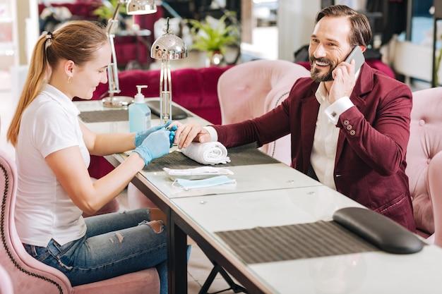 Donna che dà manicure e uomo maturo allegro che ha conversazione sul telefono