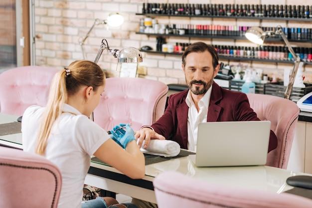 Donna che dà manicure e piacevole uomo maturo utilizzando laptop