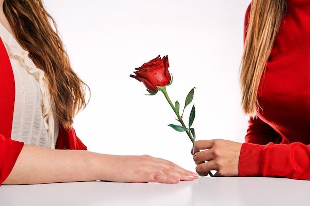 Donna che dà una rosa rossa al suo partner. concetto di amore tra donne, diversità, lgtbq e orgoglio.